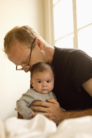 Father Kissing Baby Boy On Bed LANG_EVOIMAGES