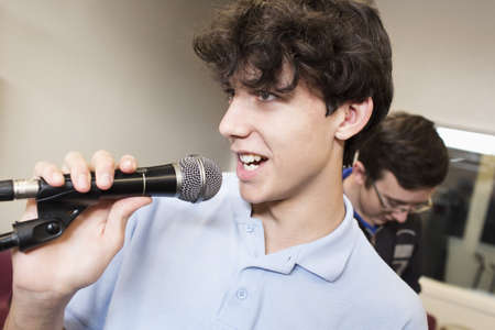 Student Singing Into Microphone In High School Band Class