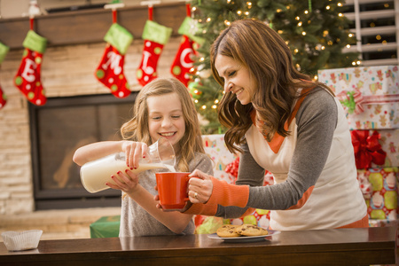 Caucasian Mother And Daughter Leaving Cookies And Milk For Santa At Christmas