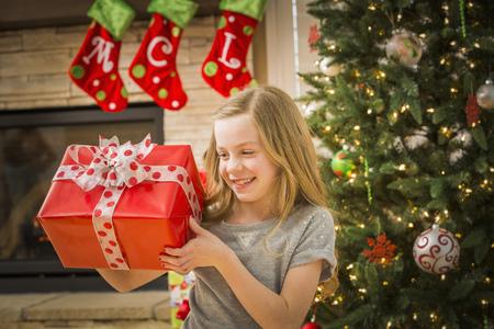 Caucasian Girl Examining Christmas Gift LANG_EVOIMAGES