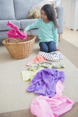 Mixed Race Girl Sorting Laundry On Living Room Floor