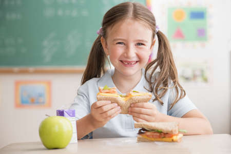 Caucasian Student Eating Lunch In Classroom
