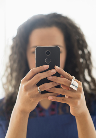 Close Up Of Mixed Race Woman Using Cell Phone LANG_EVOIMAGES