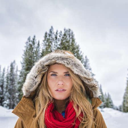 Caucasian Woman Wearing Fur Parka Hood In Snowy Forest