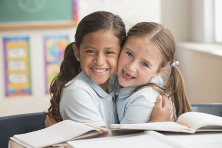 Smiling Students Hugging In Classroom