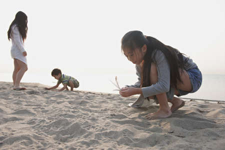 Chinese Brother And Sisters Exploring Sand On Beach LANG_EVOIMAGES