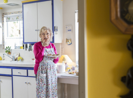 Older Caucasian Woman Eating In Kitchen LANG_EVOIMAGES