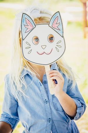 Caucasian Girl Holding Cat Mask LANG_EVOIMAGES