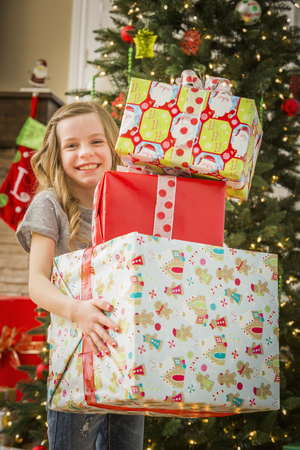 Caucasian Girl Holding Pile Of Christmas Gifts LANG_EVOIMAGES