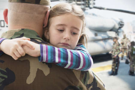 Caucasian Soldier Hugging Sad Daughter Near Helicopter