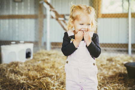 Caucasian Girl Biting Fingers In Barn