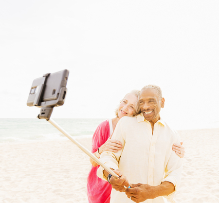 Older Couple Taking Cell Phone Photograph On Beach LANG_EVOIMAGES