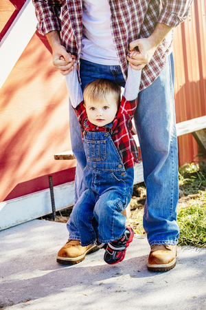 Caucasian Father And Son Playing Outside Barn LANG_EVOIMAGES