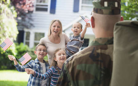 Caucasian Family Greeting Returning Soldier Father LANG_EVOIMAGES