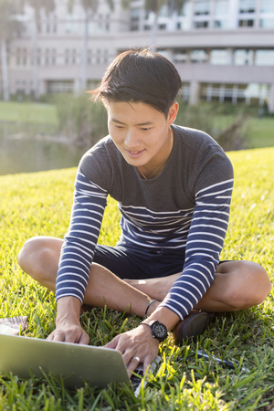 Korean Man Using Laptop In Grass