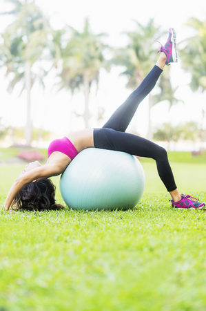 Chinese Woman Stretching On Fitness Ball In Park LANG_EVOIMAGES