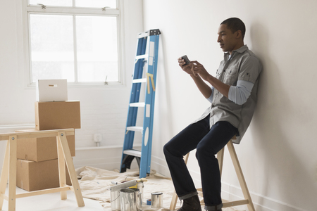 Black Man Sitting In Room Under Renovation LANG_EVOIMAGES