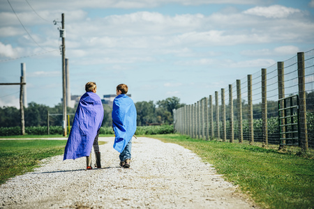 Caucasian Children Wearing Capes On Dirt Road