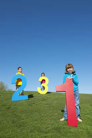 Children Playing With Large Numbers In Field LANG_EVOIMAGES