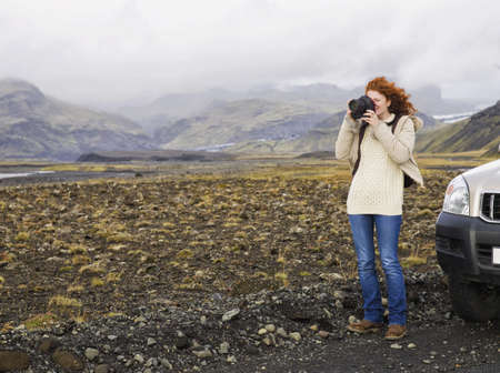 Caucasian Woman Photographing On Remote Road LANG_EVOIMAGES