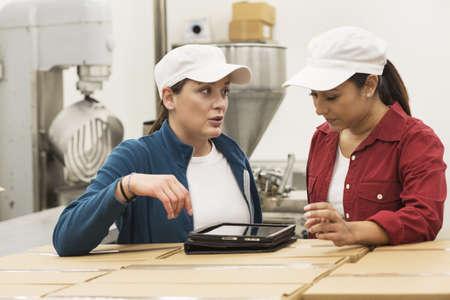 Workers Using Digital Tablet On Cardboard Boxes In Factory