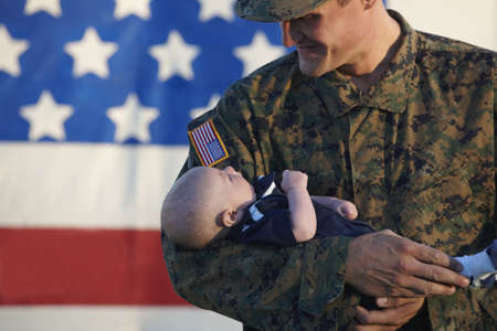 Caucasian Soldier Cradling Newborn Baby Near American Flag