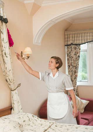 Caucasian Maid Dusting In Hotel Room