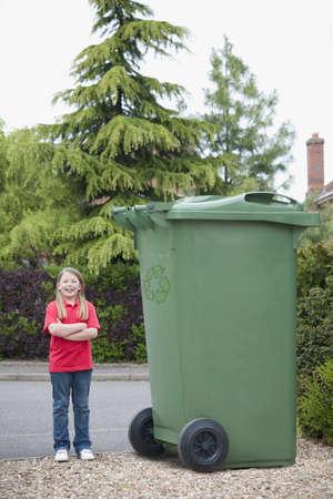 Caucasian Teenage Girl Smiling Near Large Recycling Bin LANG_EVOIMAGES