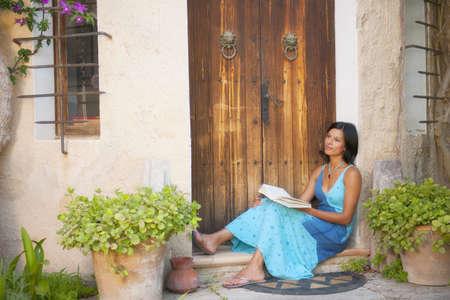 Hispanic Woman Reading Book In Doorway