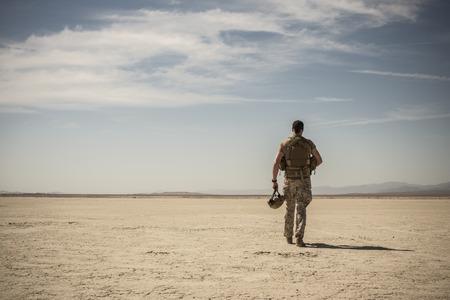 Soldier Walking In Remote Desert LANG_EVOIMAGES