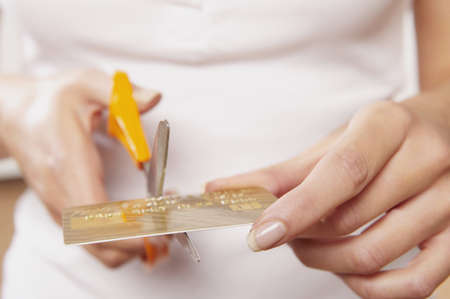Caucasian Woman Cutting Credit Card LANG_EVOIMAGES