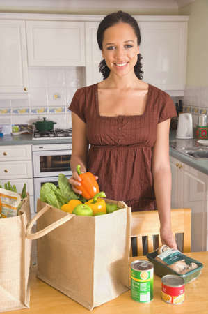 Mixed Race Woman Unpacking Groceries In Kitchen