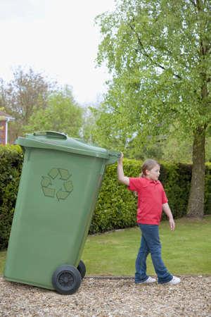 Caucasian Teenage Girl Wheeling Large Recycling Bin