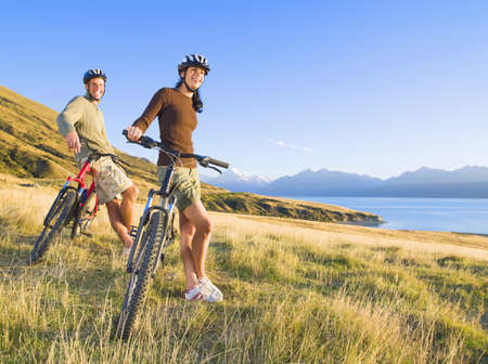 Couple Leaning On Mountain Bikes In Remote Field