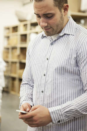 Caucasian Man Using Cell Phone In Warehouse
