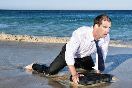 Wet Caucasian Businessman Crawling On Beach With Briefcase
