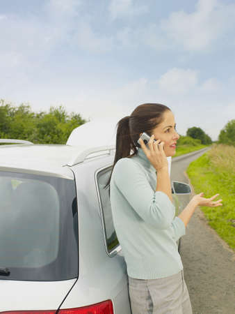 Caucasian Businesswoman Calling For Help From Broken Down Car On Rural Road LANG_EVOIMAGES