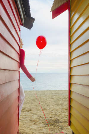 Caucasian woman carrying balloon on beach near colorful huts LANG_EVOIMAGES