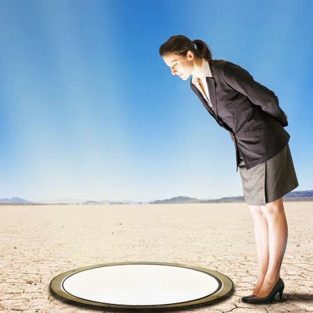 Caucasian businesswoman peering into glowing hole in desert landscape