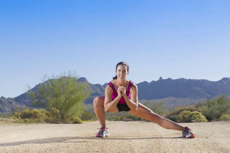 Caucasian runner stretching on remote dirt road