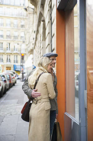 Caucasian couple window shopping in urban store LANG_EVOIMAGES