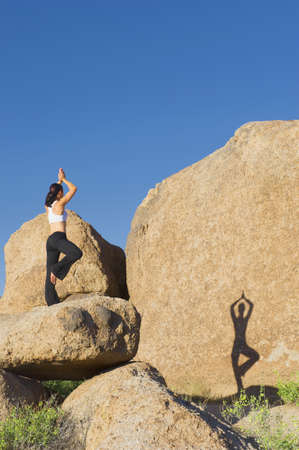 Shadow of Caucasian woman practicing yoga on rock formation
