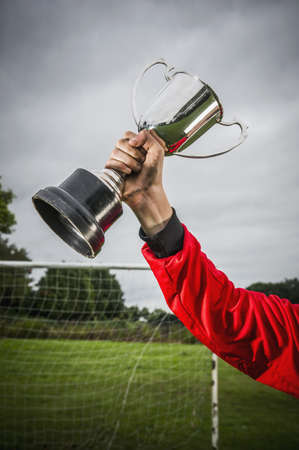 Dirty Caucasian soccer player holding trophy in field