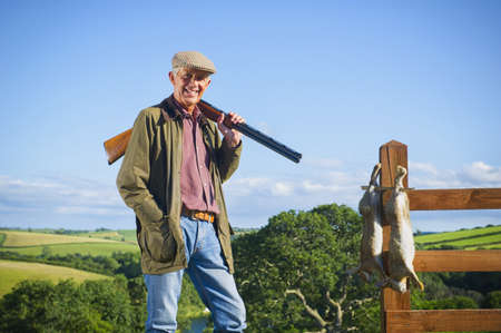 Caucasian man with shotgun and rabbits in rural field LANG_EVOIMAGES