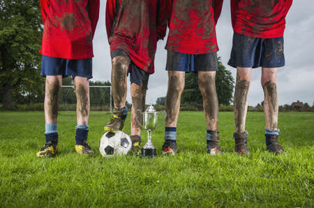 Dirty Caucasian soccer team with trophy and ball in field