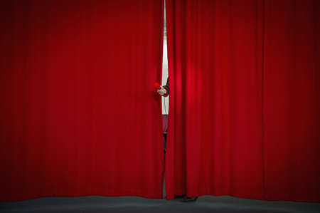 Caucasian businessman holding microphone from behind curtain LANG_EVOIMAGES
