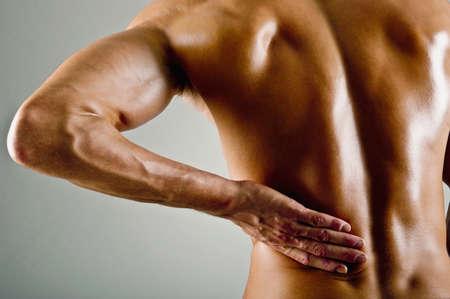 Caucasian athlete rubbing painful back muscles LANG_EVOIMAGES