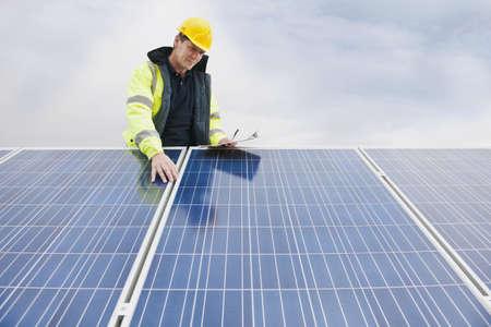 Caucasian technician examining solar panels LANG_EVOIMAGES