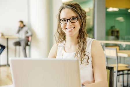 Caucasian businesswoman using laptop in cafe