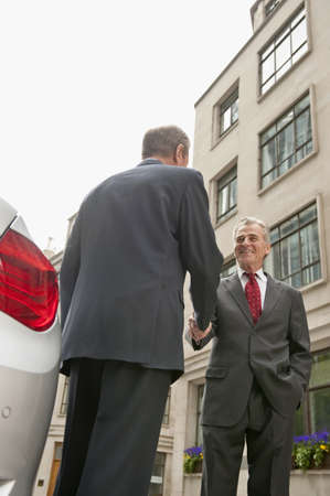 Caucasian businessmen shaking hands near car LANG_EVOIMAGES